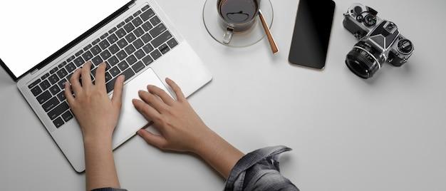 モックアップのラップトップ、スマートフォン、カメラを備えたワークスペースで働く女性