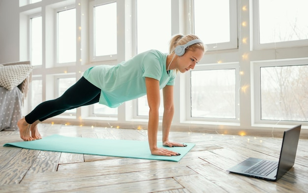 Female working out on mat and watching video on laptop