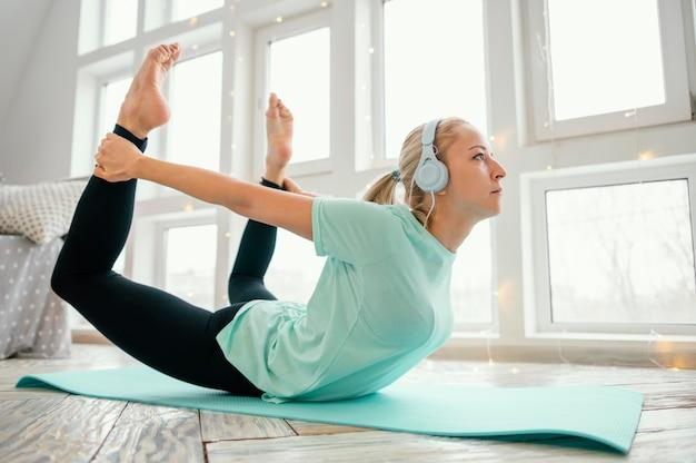 여성 매트 운동 및 음악 듣기