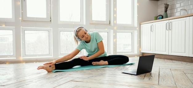 Женщина работает на коврике и смотрит видео на ноутбуке