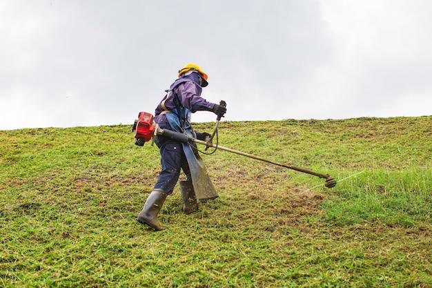 여성 작업복 보호복은 잔디 깎는 기계로 언덕 잔디를 깎는다