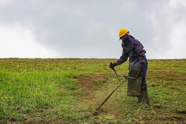 女性の作業服保護服は、芝刈り機で芝生の草を丘の上で刈り取ります