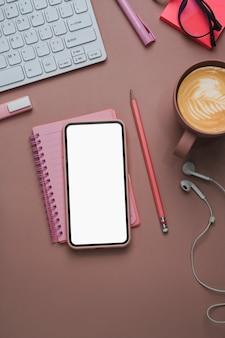 Female workplace with mobile phone notebook, coffee cup and office supplies on pink background.