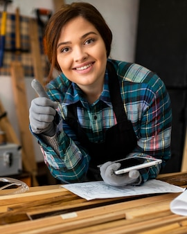 Female in workshop holding tablet and showing ok sign