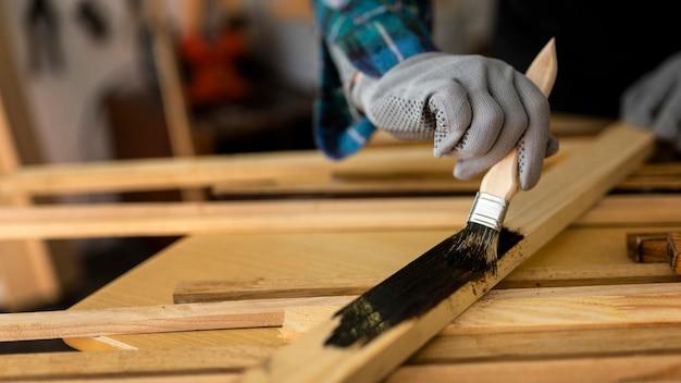 Female in workshop painting wood plank