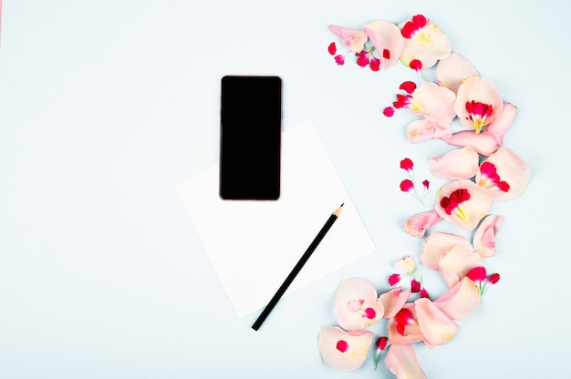 Female workspace with flowers and paper card. top view feminine background.
