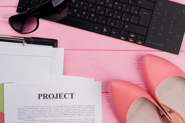 Female workspace with keyboard sun glasses shoes different papers on pink background