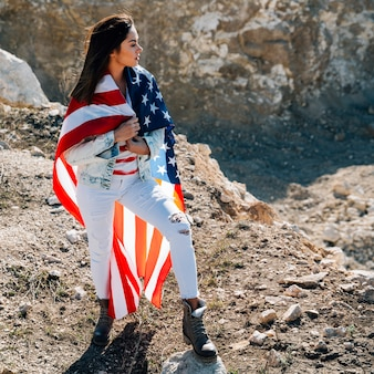 Female wrapped in flag standing on mountain