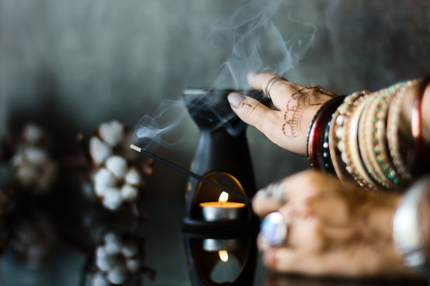 Female wrists painted with henna traditional indian oriental mehndi ornaments. hands dressed in metal bracelets and rings holding aromatic stick. aroma lamp and cotton flowers on background.