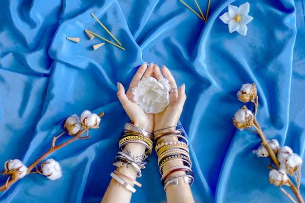 Female wrists painted with traditional indian oriental mehndi ornaments by henna. hands dressed in bracelets and rings hold white flower. blue fabric with folds and cotton branches on background.