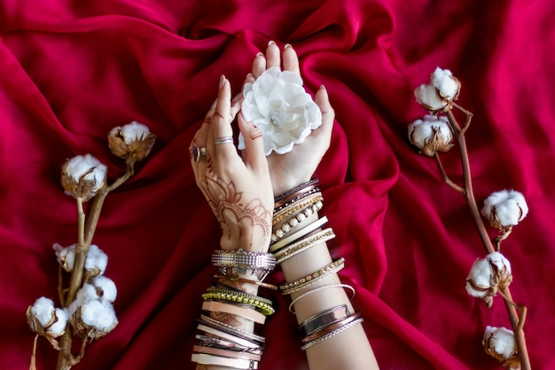 Female wrists painted with traditional indian oriental mehndi ornaments by henna. hands dressed in bracelets and rings hold white flower. vinous fabric with folds and cotton branches on background.
