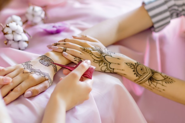 Female wrists painted with traditional oriental mehndi ornaments. process of painting womens hands with henna, preparing for indian wedding. pink fabric with folds, flowers and candles on background.