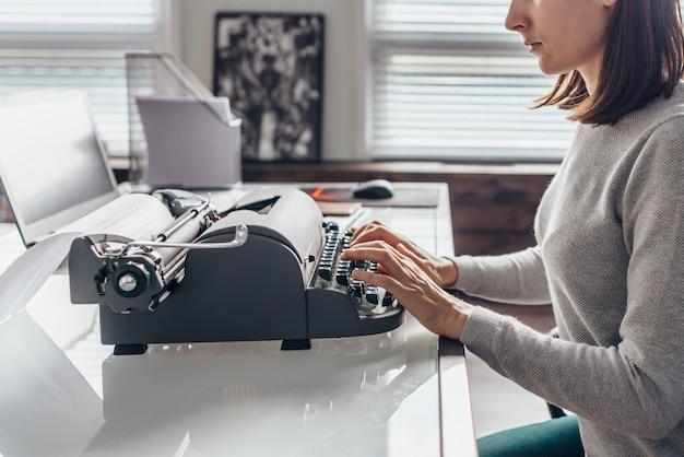 Female writer typing on a typewriter sitting in her workroom.