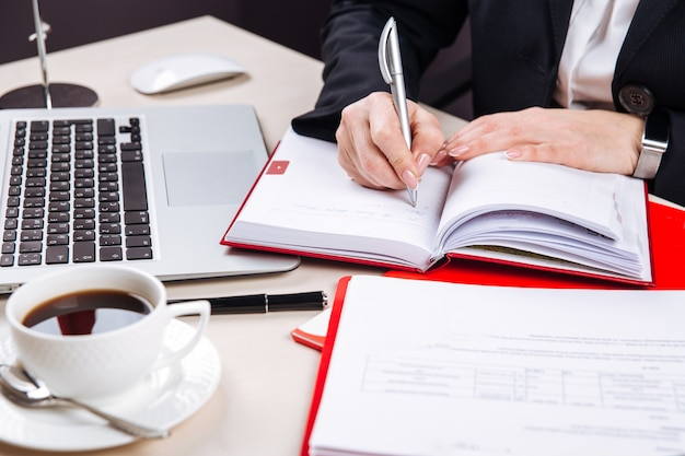 Female writing in daily planner coffee and laptop