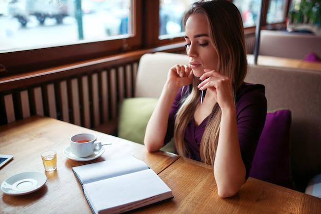 レストランでノートに書く女性。
