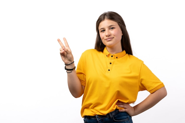 Femmina in camicia gialla e blue jeans in posa e sorridente sui vestiti di modello donna sfondo bianco