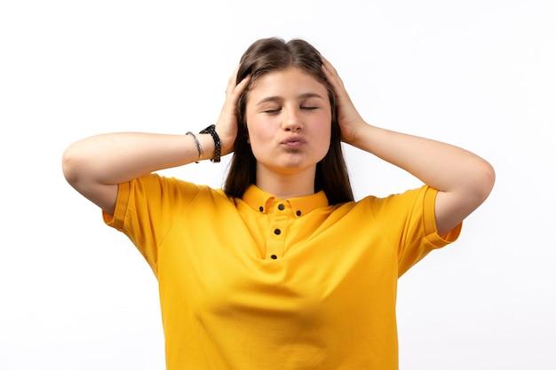 Femmina in camicia gialla e blue jeans in posa con espressione civetta sui vestiti di modello di donna sfondo bianco