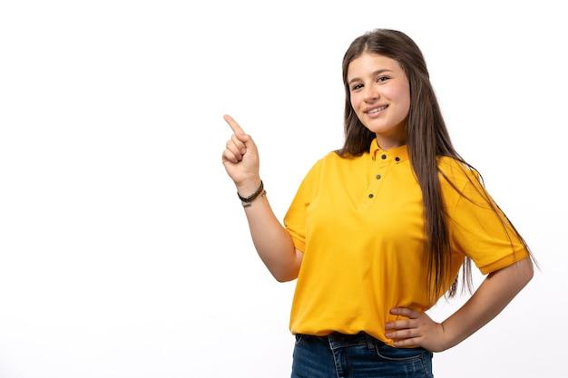 Femmina in camicia gialla e blue jeans in posa con felice espressione sui vestiti di modello donna sfondo bianco