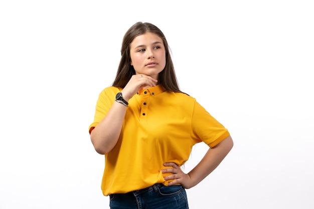 Femmina in camicia gialla e blue jeans in posa con espressione di pensiero sui vestiti di modello di donna sfondo bianco