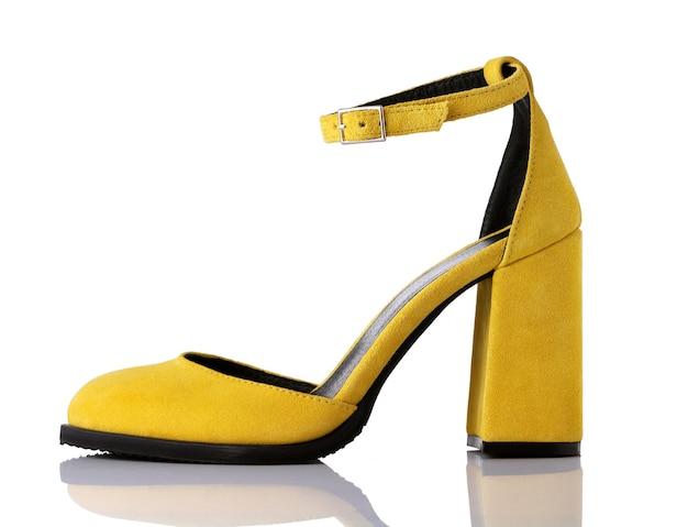 白い背景の上の女性の黄色いスエードハイヒールの靴