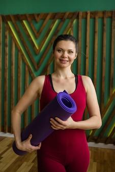 ブルゴーニュのスポーツユニフォームの女性のヨギは、ジムで紫色のマットを保持しています