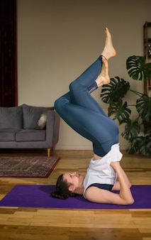 Female yogi in sportswear performs an inverted pose on a mat in a room