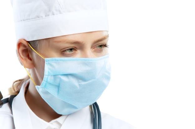 Молодая женщина-врач со стетоскопом и маской, изолированной на белой стене