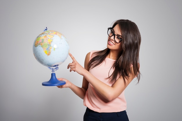 Female young teacher holding globe