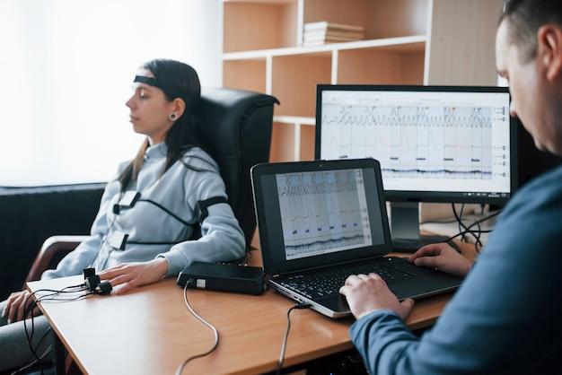 Женский молодой кражи. девушка проходит детектор лжи в офисе. задавать вопросы. проверка на полиграфе