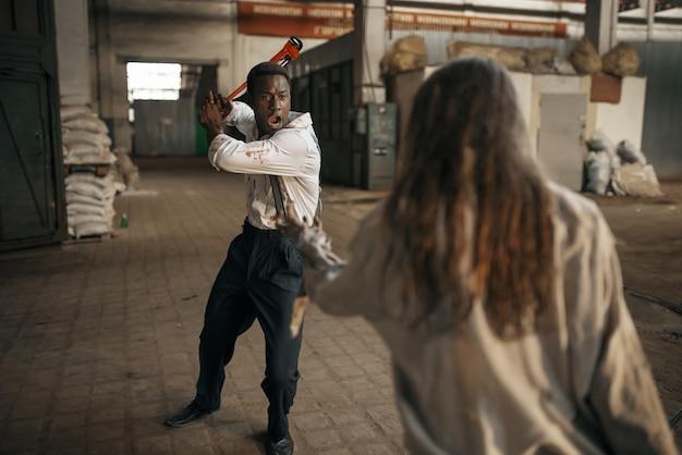 Зомби-женщина борется с безнадежным мужчиной на заброшенной фабрике. ужас в городе, жуткие ползания, апокалипсис судного дня, кровавые злые монстры