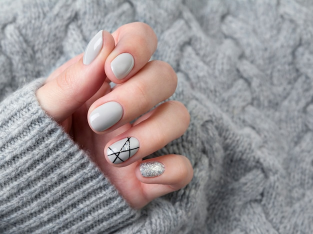 Females hand in gray knitted sweater with modern manicure close up
