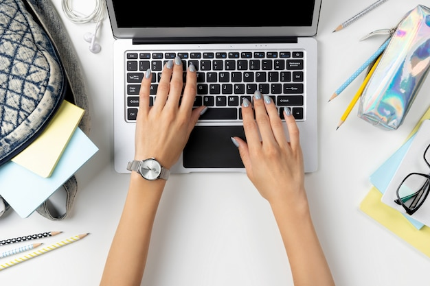 Females hands working on modern laptop with backpack and stationery