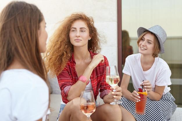 Femmine in possesso di bicchieri di vino e cocktail divertendosi insieme