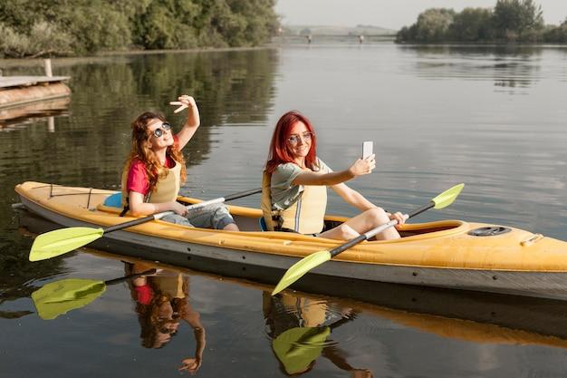 Femmine in kayak che prendono selfie