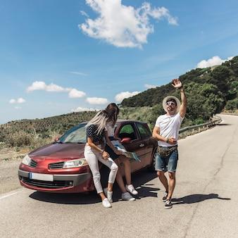 彼女の男性の友人が何かを探している間に地図を見て車に傾いている女性