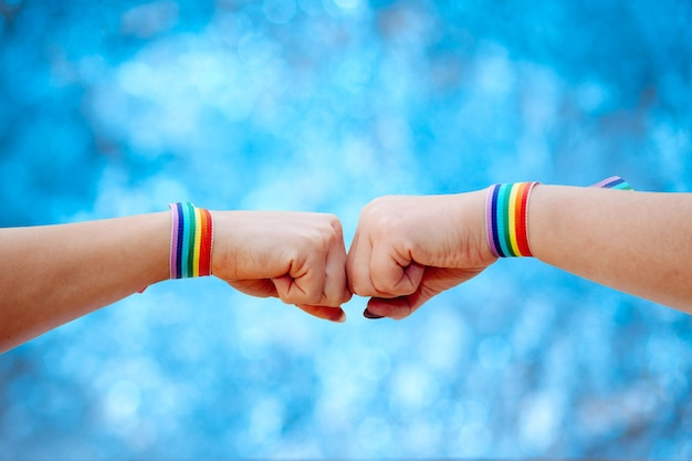 A females making hand sign with rainbow colours wristband on blurred background