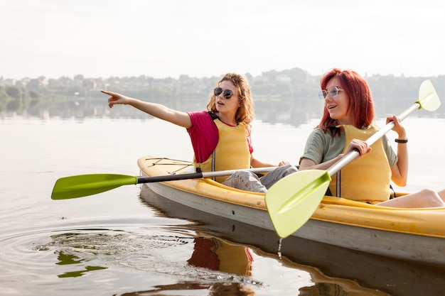 Females rowing in kayak on lake