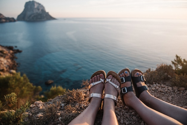 Females sitting on a cliff by the sea enjoying the beautiful view of the sunset