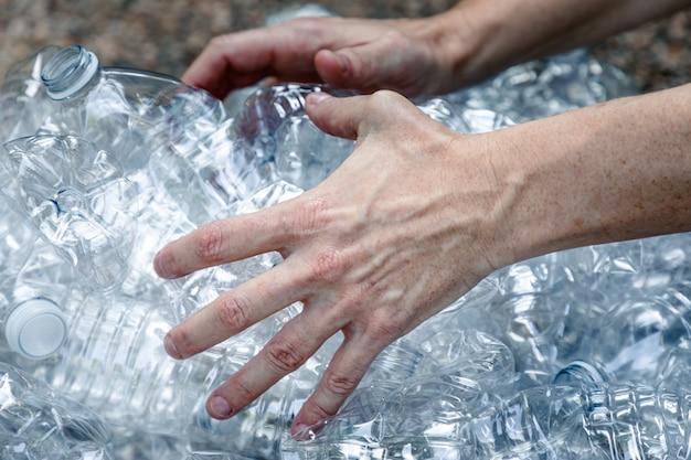 Mani di femmine che afferrano bottiglie di plastica per raccoglierle e cestinarle