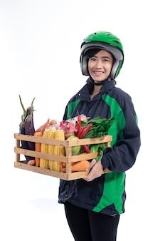 ヘルメットをかぶっているフェマン・ユーバーデリバリーは食料品を持参します