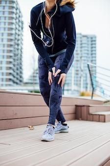 Femanle jogger, имеющий проблемы с коленом на тренировке