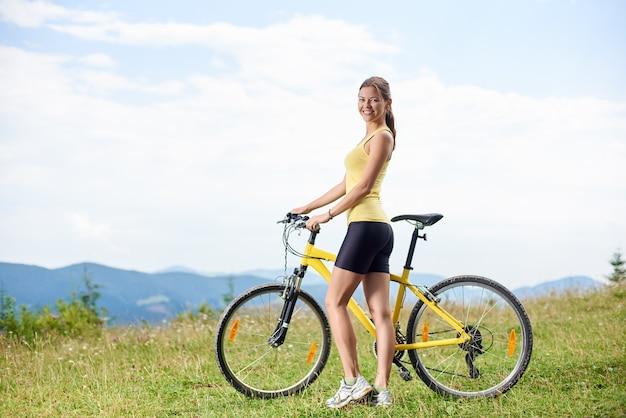 노란색 산악 자전거에 자전거를 타는 femela 사이클