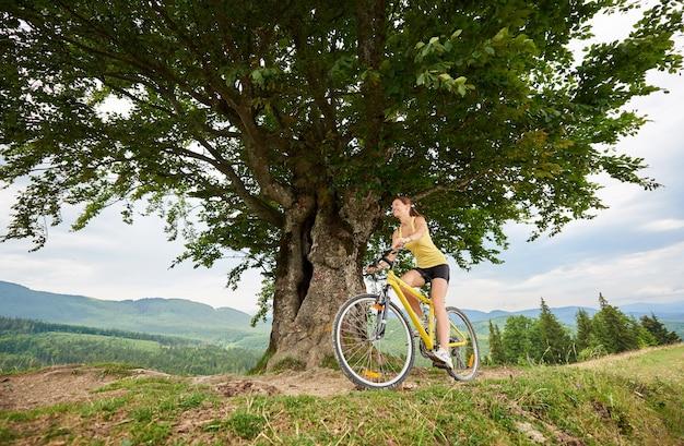 Femela cyclist cycling on yellow mountain bike