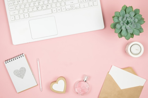 Femine office desktop with office accessories on pink surface. womens workspace with succulent, candle and cosmetics.