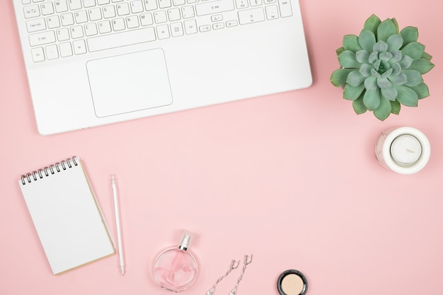 Офисный рабочий стол femine с офисными аксессуарами на розовой поверхности. женское рабочее пространство с сочными, свечными и косметическими средствами.
