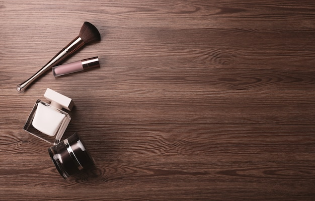 Feminine accessories, perfume brush and cosmetics on wooden background