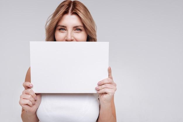 Женственно и сильно. позитивная веселая очаровательная дама использует лист бумаги, закрывающий половину лица, во время позирования