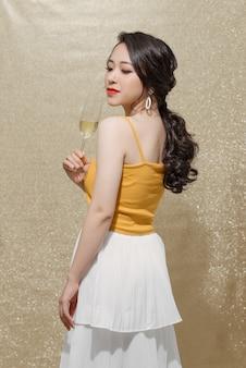 きらめく背景の上に立っているシャンパンのガラスを上げるフェミニンなアジアのモデル