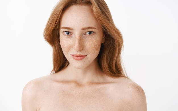 Feminine attractive adult and slim redhead female with freckles and natural ginger hair standing naked smiling sensually gazing with interest and desire