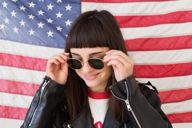 フェミニンな美しい女性または10代の少女は、アメリカの国旗、トレンディでファッショナブルなヒップスター、アメリカの愛国者の前で新しいサングラスのアイウェアを着用します